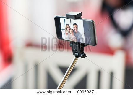 technology and people concept - close up of happy family picture on smartphone screen with selfie stick