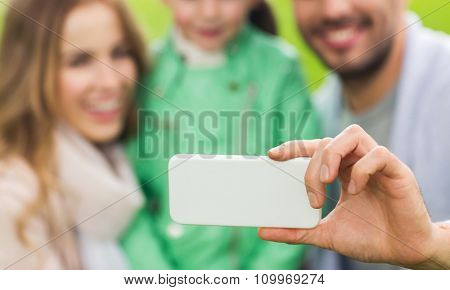family, childhood, technology and people concept - close up of happy father, mother and little daughter taking selfie by smartphone in park