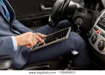 transport, business trip, technology and people concept -close up of young man with tablet pc computer driving car