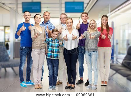 gesture, family, travel, generation and people concept - group of smiling men and women showing thumbs up over airport waiting room background