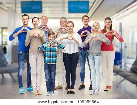 gesture, travel, tourism and people concept - happy family  showing heart shape hand sign over airport waiting room background