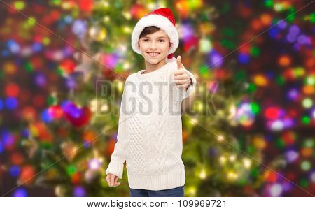 holidays, gesture, christmas, childhood and people concept - smiling happy boy in santa hat showing thumbs up over holidays lights background