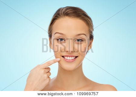 beauty, people, dental care and hygiene concept - happy young woman pointing finger to her smile or teeth over blue background