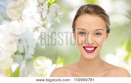 beauty, people and health concept - smiling young woman face with pink lipstick on lips and shoulders over summer green natural background with cherry blossom