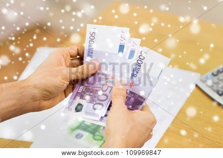savings, finances, economy and home concept - close up of man hands counting money at home over snow effect