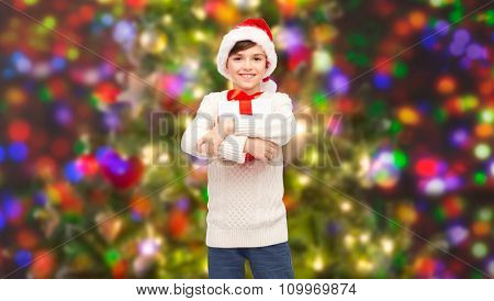 holidays, presents, christmas, childhood and people concept - smiling happy boy in santa hat with gift box over holidays lights background