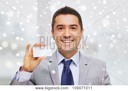 business, people and office concept - smiling businessman in suit showing blank white visiting card over snow effect