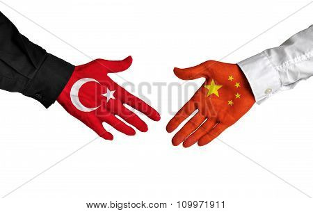 Turkey and China leaders shaking hands on a deal agreement