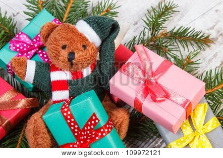 Teddy Bear With Colorful Gifts For Christmas And Spruce Branches
