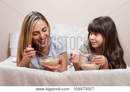 Mother and daughter are talking and having breakfast