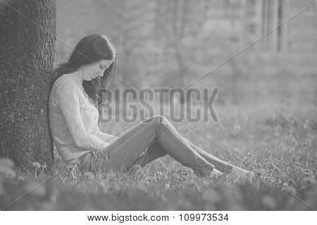 The Lonely Girl Sits At A Tree. The Photo In Old Black-and-white