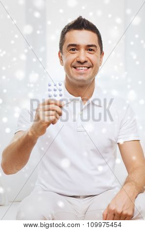 people, medication, medicine and health care concept - happy man showing pack of pills at home over snow effect