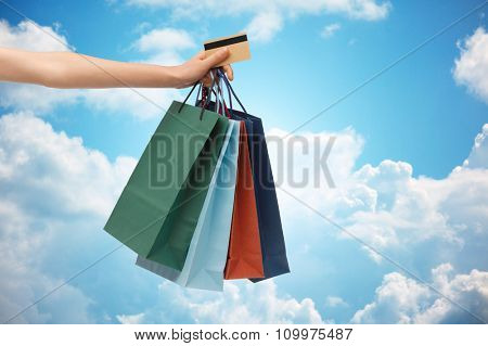 people, sale and consumerism concept - close up of woman with shopping bags and bank or credit card over blue sky and clouds background