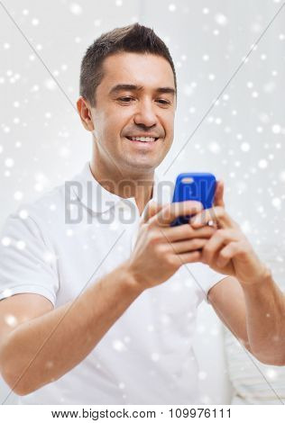 technology, people, lifestyle and communication concept - happy man with smartphone at home over snow effect