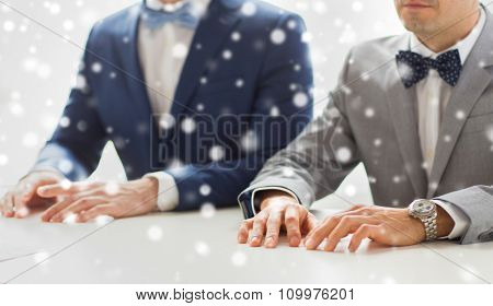 people, homosexuality, same-sex marriage and love concept - close up of happy male gay couple hands on wedding over snow effect
