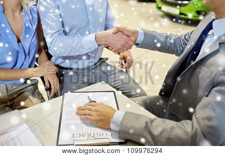 auto business, car sale, gesture and people concept - close up of customers couple with dealer shaking hands in auto show or salon over snow effect