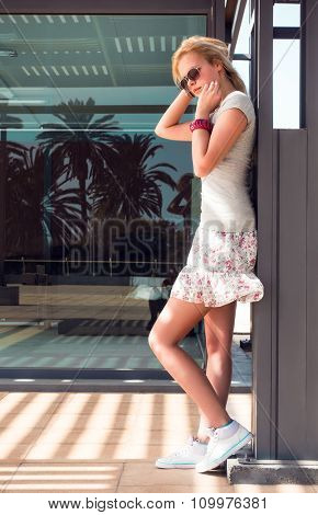 A young woman wearing a short skirt near to a showcase, toned photo