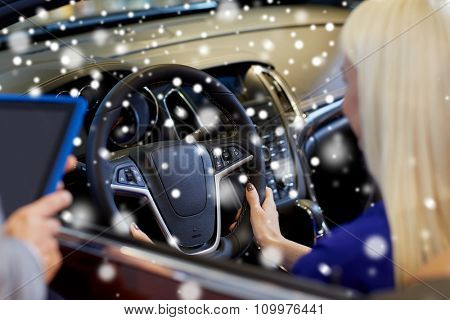 auto business, car sale, technology and people concept - close up of woman and car dealer hands with tablet pc computer in auto show or salon over snow effect