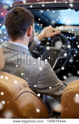 auto business, car sale, lifestyle and people concept - close up of man sitting in cabrio car at auto show or salon over snow effect