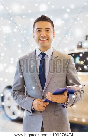 auto business, car sale, consumerism and people concept - happy man with clipboard at auto show or salon over snow effect