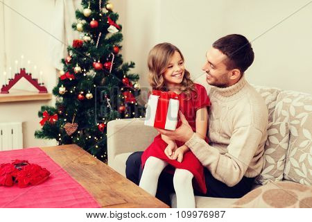 christmas, x-mas, winter, happiness and people concept - smiling father and daughter holding gift box and looking at each other