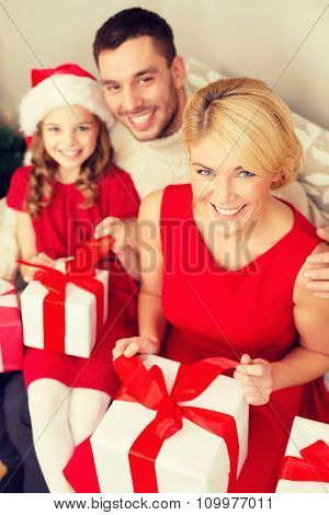 family, christmas, x-mas, happiness and people concept - happy family opening gift boxes