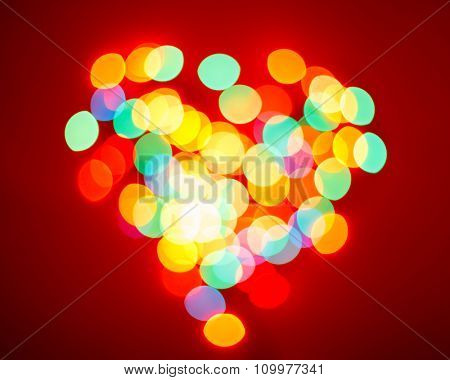 Blurred lights in a shape of a heart on red valentine background