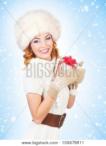 Young and beautiful woman with a Christmas present over winter background with snow.