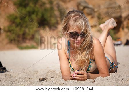 Blonde Woman Lying On The Sand On The Beach