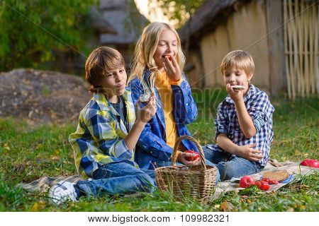 Happy smiling boy and girl lying together on rug. picnic outdoor concept