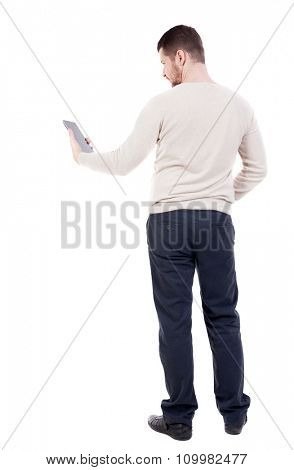 back view of standing young man with tablet computer in the hands of. Rear view people collection.  backside view of person.  Isolated over white background.