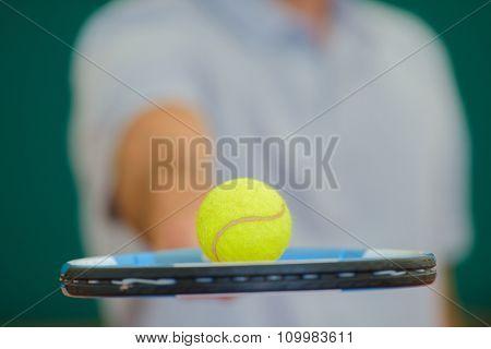 Closeup of tennis ball balancing on racket