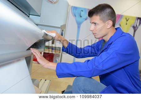 Young man loading new roll into industrial printer