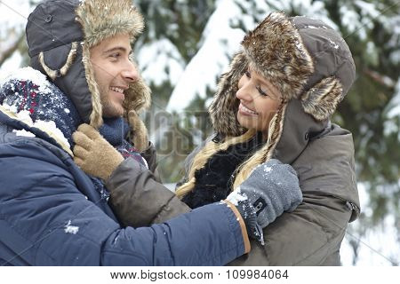 Outdoor photo of loving couple embracing at wintertime, smiling happy.