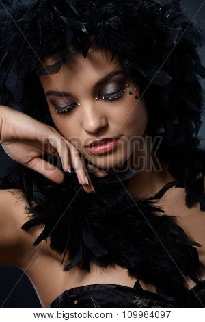 Elegant beauty wearing fancy makeup and feather boa posing with eyes closed.