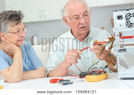 Retired man testing computer with multimeter