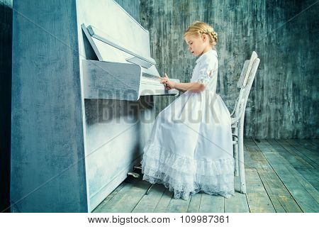 Romantic little girl in white dress playing the piano. Music and art concept. Retro style.