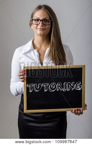 Tutoring - Young Businesswoman Holding Chalkboard With Text
