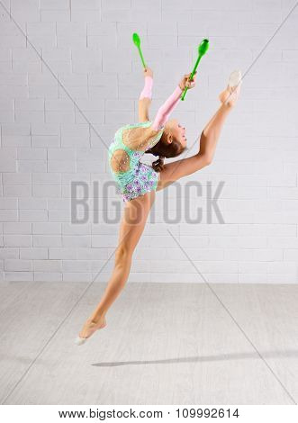 Young girl is engaged in art gymnastics on grey wall