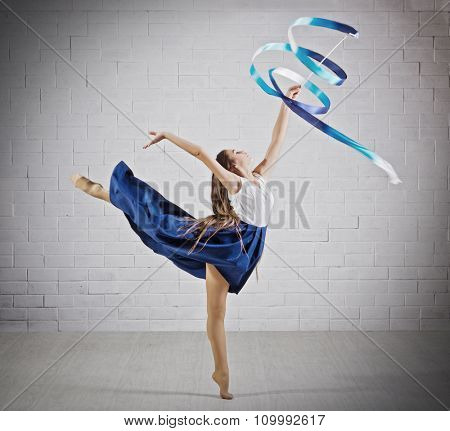Young girl is engaged in art gymnastics on grey wall (dark ver)
