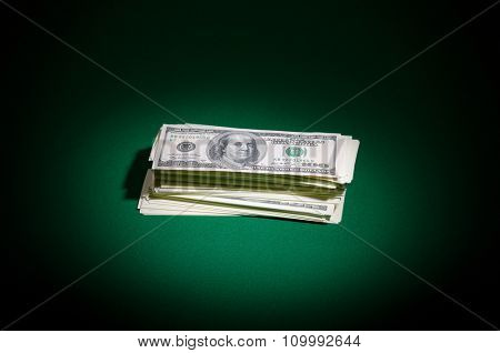 Stack of dollars on green table
