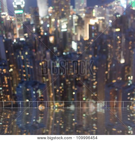 Background of blurred skyscrapers at night with reflection on the roof of building in Hong Kong, shallow depth of focus.