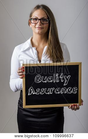 Quality Assurance - Young Businesswoman Holding Chalkboard With Text
