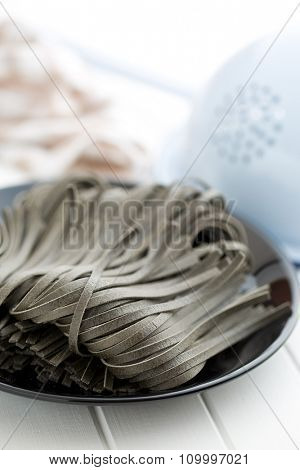 black noodles with squid sepia ink on black plate