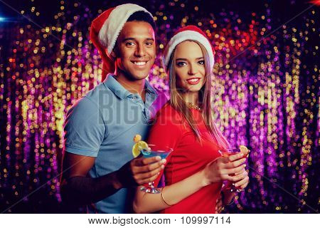 Christmas with cocktails looking at camera in night club
