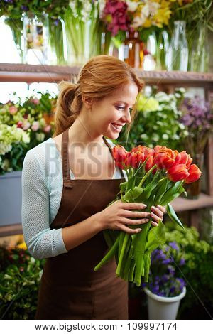Happy woman with bunch of tulips working in floral shop