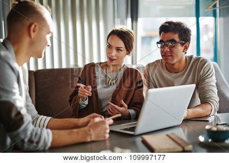 Happy young friends or employees talking at meeting