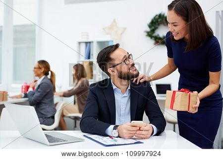 Asian businesswoman giving her boss Christmas present in office