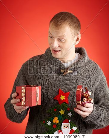 Surprised man looking into open gift-box in his hands