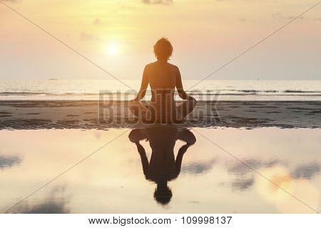 Silhouette meditation girl on the background of the stunning sea and sunset.